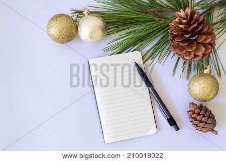 Preparing for the New year. Blank notepad with pencil and Christmas balls on white background. Fir branch and cones.