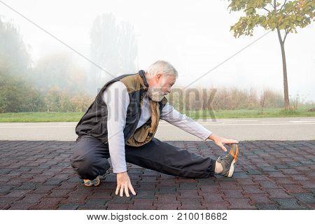 Elderly man doing physical exercise in the morning in park