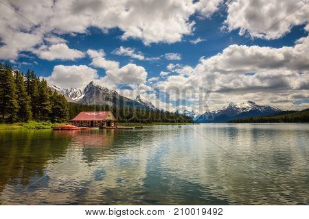 Boat house and the idyllic Maligne Lake in Jasper National Park, Canada, with snow-covered peaks of canadian Rocky Mountains in the background.