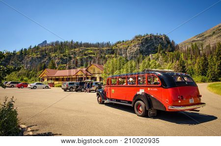 GLACIER NATIONAL PARK, MONTANA, USA - JULY 5, 2017 : : Iconic  Red Bus with tourists at the Rising Sun Motor Inn  near Saint Mary Lake in Glacier National Park.