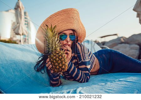 Beautiful woman in a hat and sunglasses lies on a beach chaise.
