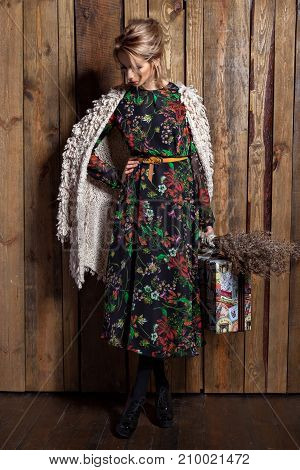Young stylish slender blond girl with red lips dressed in a dress with flowers and a cape with a suitcase stands on a  wooden background filmed in the studio with pulsed light