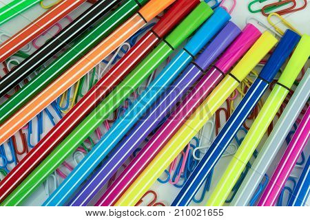 multicolored paper clips and markers randomly scattered on white paper abstract background