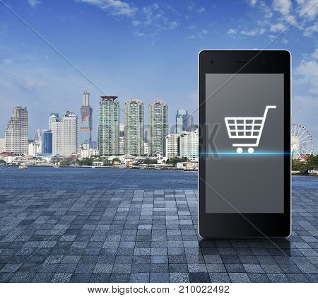 Shopping cart icon on modern smart phone screen on stone tile floor over city tower river and blue sky Shop online concept