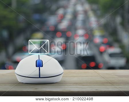 Mail flat icon with wireless computer mouse on wooden table over blur of rush hour with cars and road Contact us concept