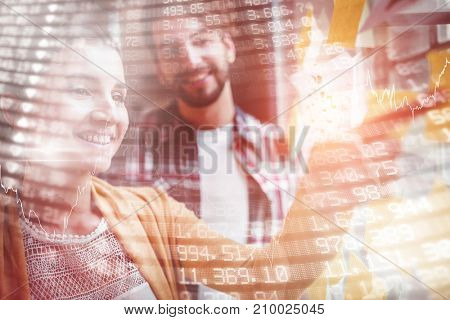 Stocks and shares against businesswoman pointing at sticky notes while explaining colleague