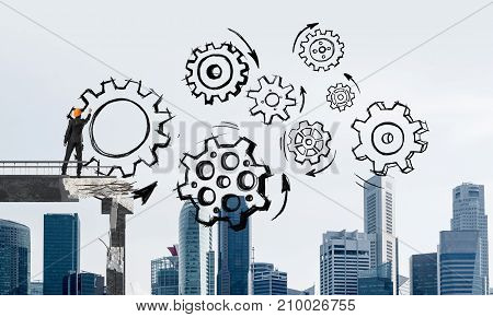 Businessman in helmet drawing sketches of gear mechanism while standing on broken bridge with cityscape on background. 3D rendering.