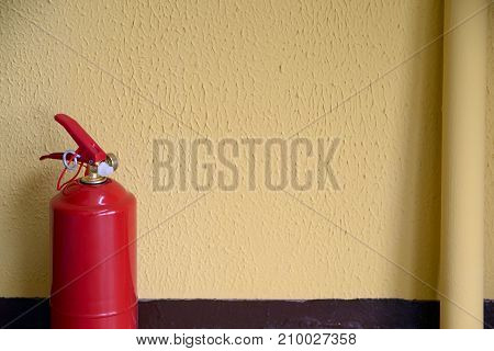Powder fire extinguisher on a yellow wall background