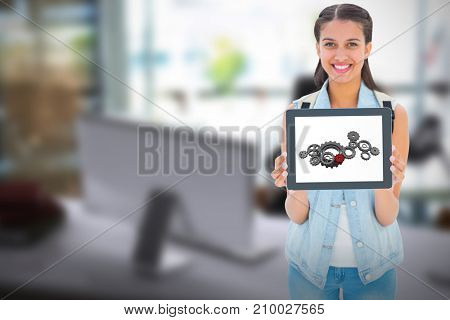 Student showing tablet pc against blurry picture of computer on desk