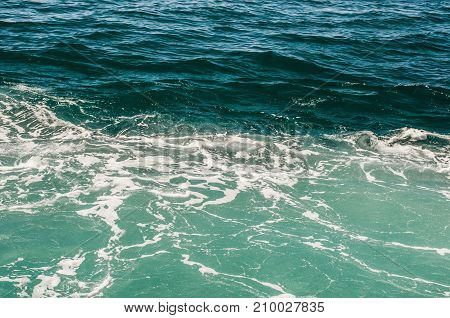 Green and azure surface of the sea with white foam