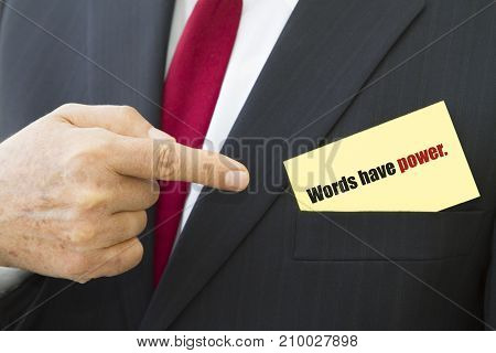 Businessman showing a card with text WORDS HAVE POWER.