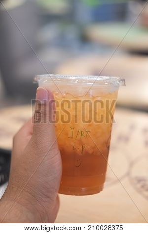 Young Man Holding Ice Lemon Tea In Plastic Glass