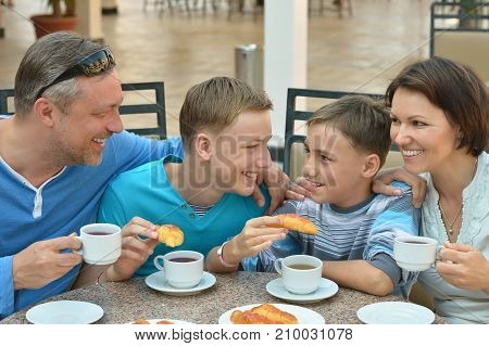 father and sons having breakfast together in outdoor cafe at resort