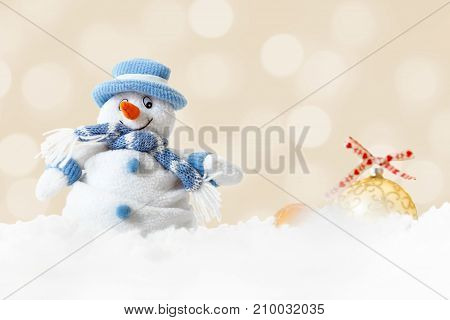 Funny handmade snowman wearing blue hat and scarf on abstract xmas lights bokeh background white soft snowflakes fall on winter landscape merry Christmas and happy new year greeting card concept