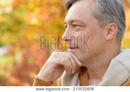 close up portrait of handsome man thinking, autumn leaves on background