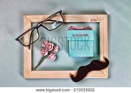 Fathers day. The inscription FOR THE BEST DAD on a self-made gift box the symbols of Father's Day are glasses mustaches roses. CONCEPT OF GREETINGS AND GIFTS. Composition in a frame.