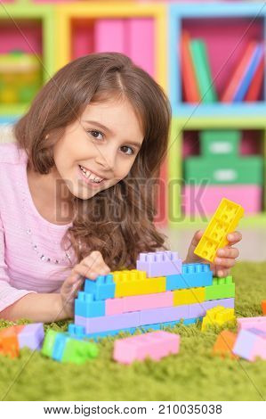 Cute girl playing with colorful plastic blocks on floor