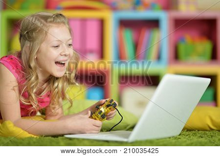 Adorable little girl using modern laptop and playing game