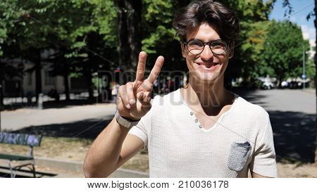 Handsome young man at city park doing victory sign with fingers, smiling satisfied to the camera