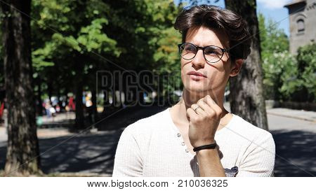 Confused or doubtful young man scratching his head and looking up. Outoodr on the street