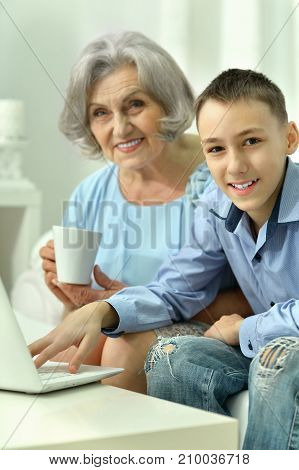 Senior woman with her grandson using laptop together