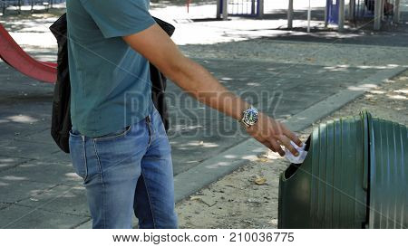 Young handsome man tossing junk in garbage bin in a park while walking around
