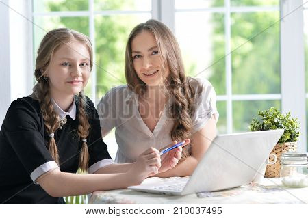 Mother and daughter with modern laptop in room