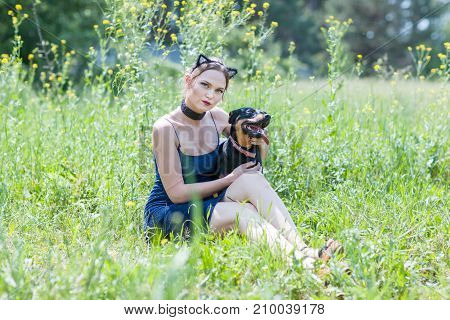 Cute girl and dog are sitting on the grass in the field