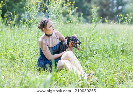 Adorable girl and dog are sitting on the grass in the field