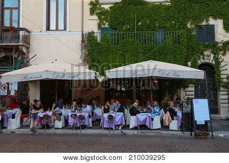 ROME, ITALY - APRIL 12, 2017: People enjoy their lunch at one of the many restaurants in Navona Square, Rome