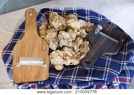 White Truffles On Cloth With Truffle Cut In Wood