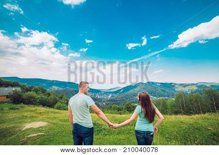 Young couple rest on the mountain peak. And loking to each other