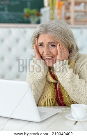 Emotional senior woman sitting at table with laptop