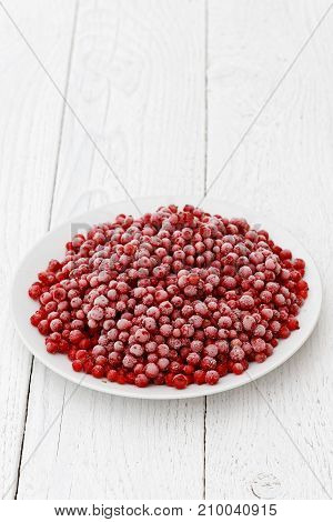 Frozen Redcurrants On White Ceramic Plate Isolated On White Painted Table.