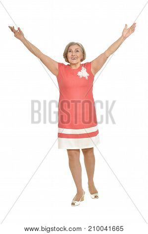 Beautiful senior woman with raised hands in pink dress isolated on white background