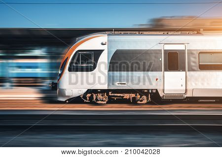 High speed train in motion at the railway station at sunset in Europe. Modern intercity train on railway platform with motion blur effect. Moving passenger train on railroad. Transportation. Vintage