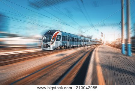High speed train in motion at the railway station at sunset in Europe. Modern intercity train on railway platform with motion blur effect. Industrial landscape. Passenger train on railroad. Vintage