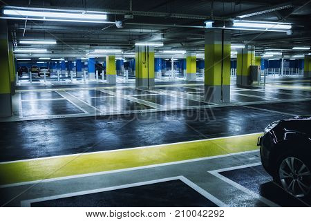 Close up on underground parking with empty slots and car