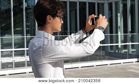 Handsome young man in city setting, taking photos with cell phone