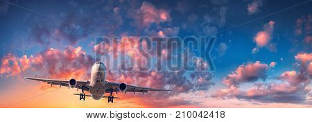 Airplane and beautiful sky. Landscape with passenger airplane is flying in the blue sky with red, purple and orange clouds at sunrise. Travel. Passenger airliner. Commercial aircraft. Private jet