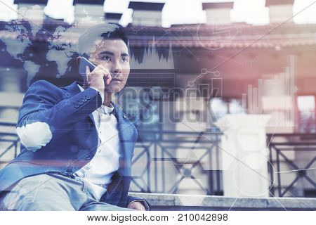 Inspired young Asian businessman is talking on his smartphone while sitting outside near a beautiful building. Toned image double exposure