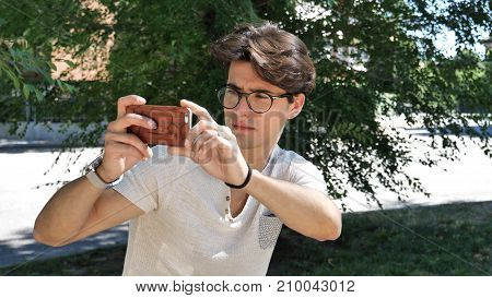 Handsome young man in city park taking photos with cell phone