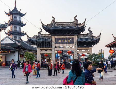 Suzhou, China - Nov 5, 2016: Shopping street at the historic Zhouzhuang Water Town. Numerous visitors can be seen walking along this path at the gate to the township.
