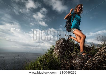 Lady tourist with backpack moving through rocky terrain with sea on the background