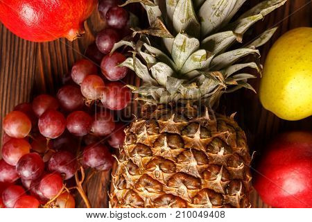 Fresh fruits on a dark wooden table. Close-up. Pineapple, grapes, apples, pomegranate. View from above