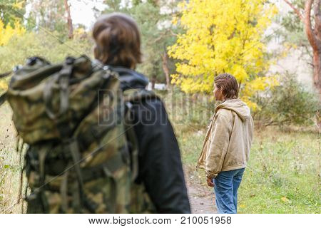 Young travelers as a couple, in the autumn forest. Close-up. The girl with a short haircut.