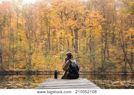 Girl sits near lake in autumn and drinks coffee. Young female person hiking at nature park rests at riverbank on gold autumn day and enjoys beautiful october scenery having a hot drink from thermos
