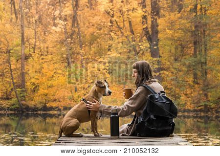 Female tourist sit with dog near lake and enjoy beautiful autumn view drinking cup of coffee. Girl and her pet staffordshire terrier hiking in the forest and have a rest at riverbank female having big cup of coffee from thermos