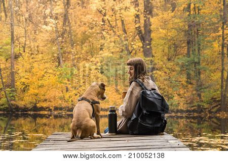 Girl hiker rests at riverbank with her pet dog and drinks coffee from thermos. Young female person and her staffordshire terrier puppy having a rest by the lake on beautiful october day of indian summer