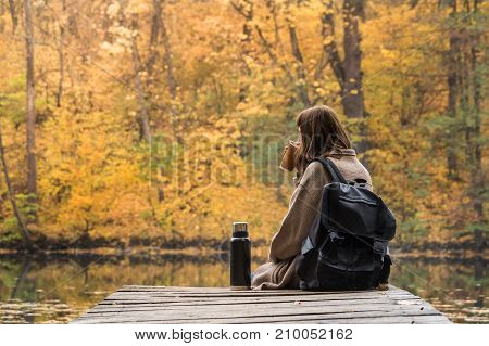 Young female hiker with backpack sits at riverbank, drinks coffee and looks at beautiful indian summer scenery. Girl having rest and hot drink from thermos near the lake at a nature park on a gold autumn day